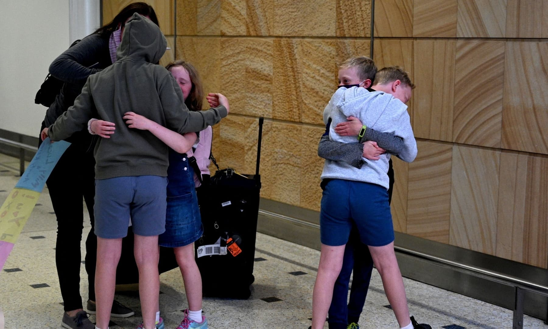 A family reunites upon their arrival from New Zealand at Sydney International Airport on April 19. — AFP