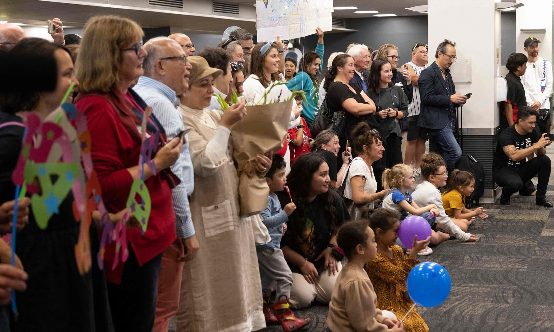 Families wait to be reunited as travellers arrive on the first flight from Sydney, in Wellington on April 19. — AFP