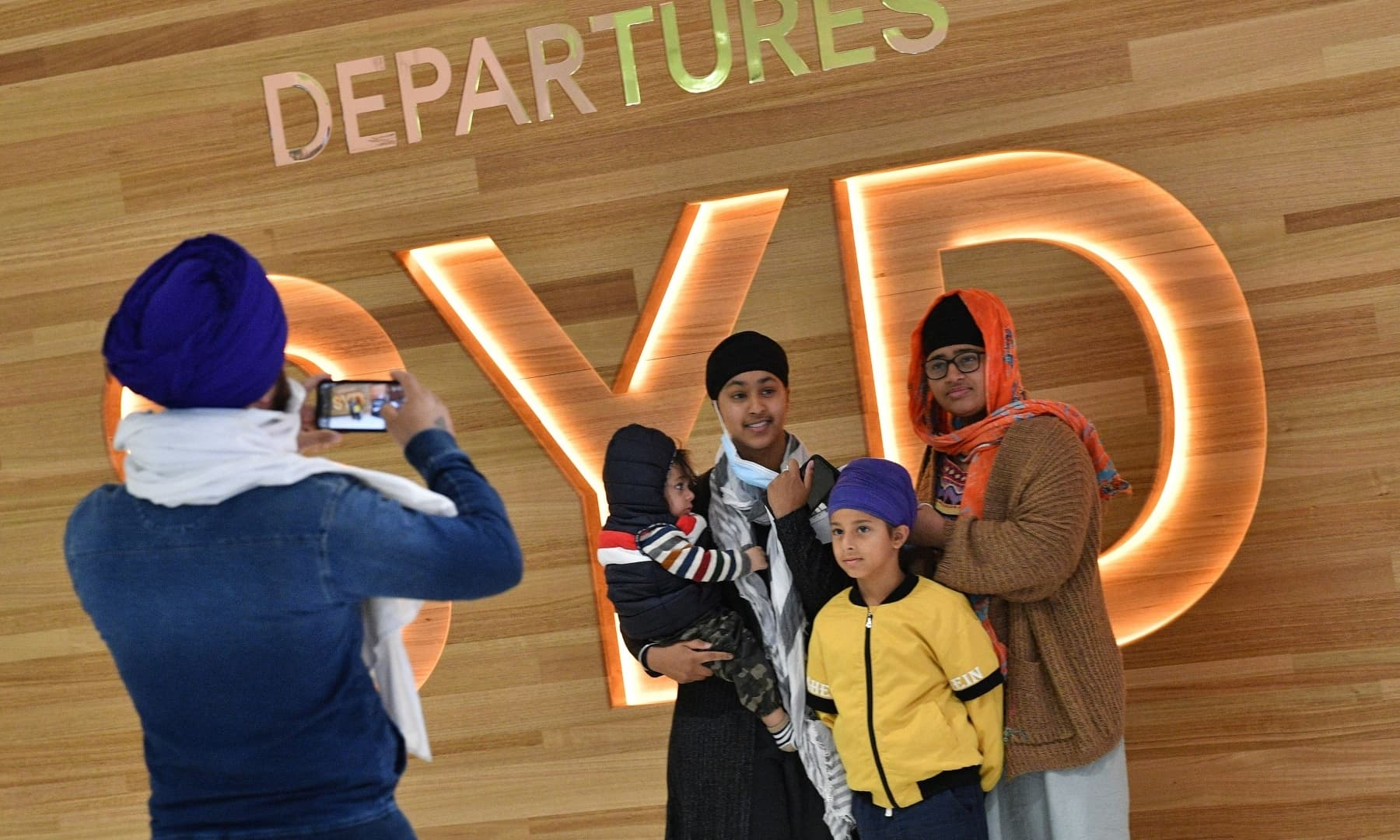 A family takes photos before their flight for New Zealand at Sydney International Airport on April 19. — AFP
