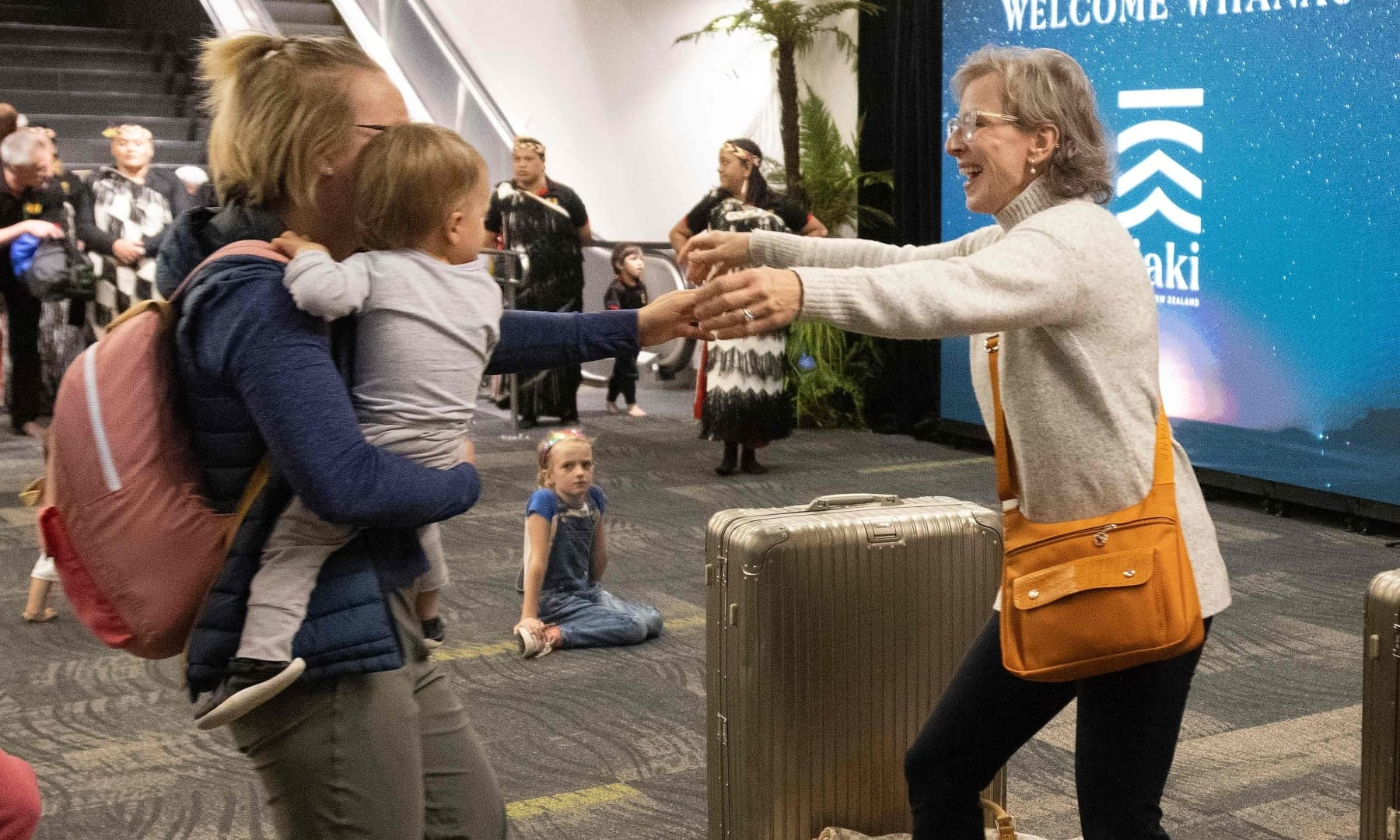 Families are reunited as travellers arrive on the first flight from Sydney, in Wellington on April 19. — AFP