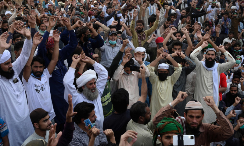 Supporters of the banned Tehreek-e-Labbaik Pakistan (TLP) party shout sloans as they block a street during a protest in Lahore on Monday. — AFP