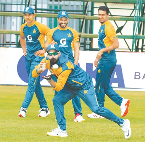 HARARE: Senior Pakistan cricketer Mohammad Hafeez prepares to take a catch as team-mates (L-R) Mohammad Hasnain, Mohammad Nawaz and Arshad Iqbal look intently during a practice session at the Harare Sports Club on Monday. —Courtesy PCB