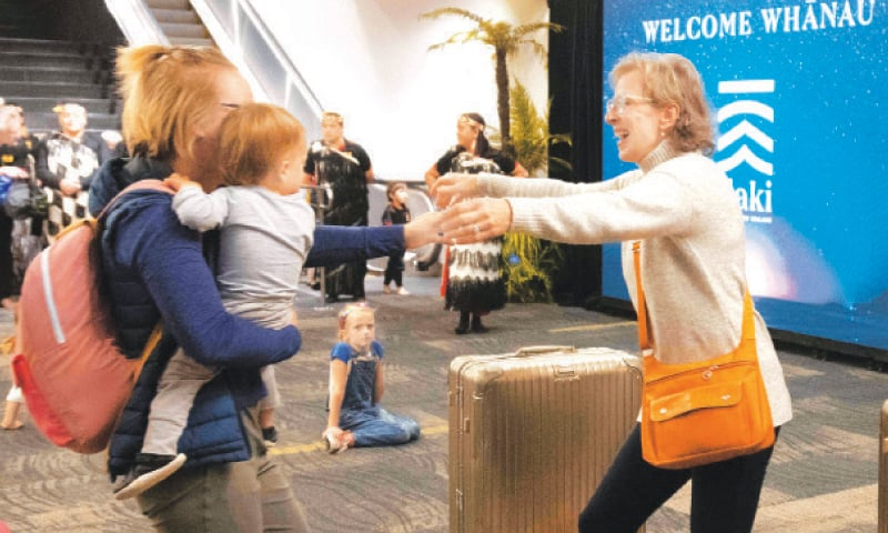 Families are reunited as travellers arrive in Wellington on the first flight from Sydney.—AFP