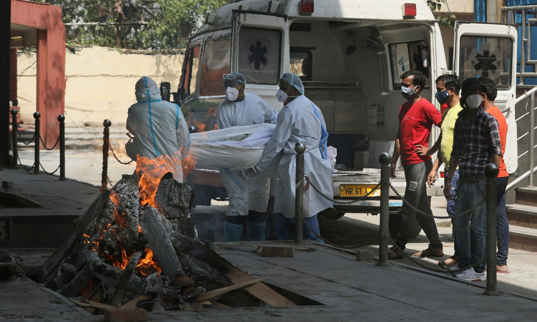Health workers carry a body of a person who died of Covid-19 for cremation in New Delhi on April 19. — AP
