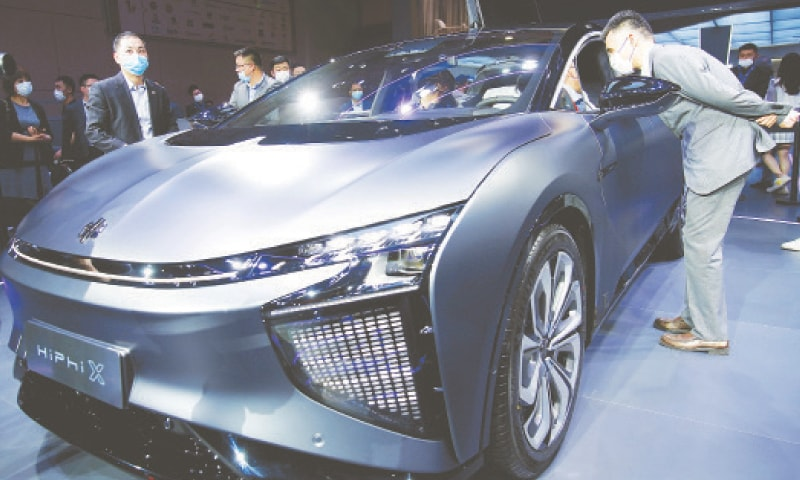 SHANGHAI: Visitors inspect a HiPhi X electric vehicle displayed during a media day for an auto show on Tuesday.—Reuters