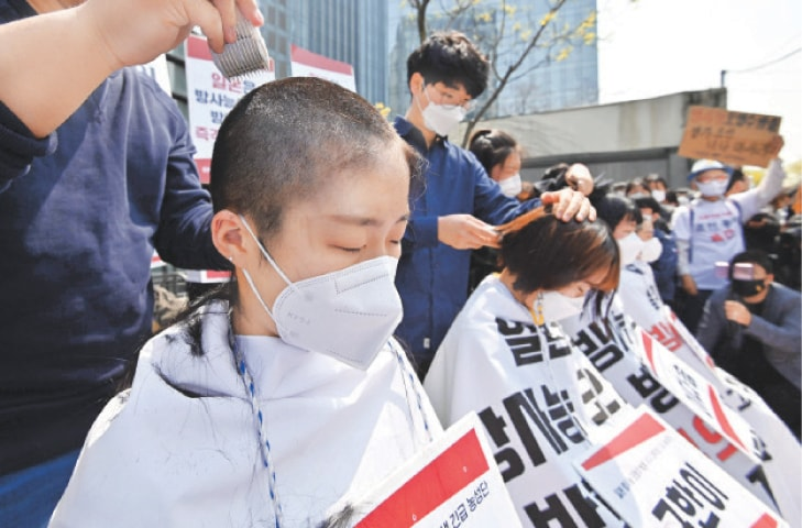 South Korean protesters have their heads shaved during a protest in front of the Japanese embassy on Tuesday against Tokyo's decision to release treated water from the stricken Fukushima Daiichi nuclear plant into the sea.—AFP