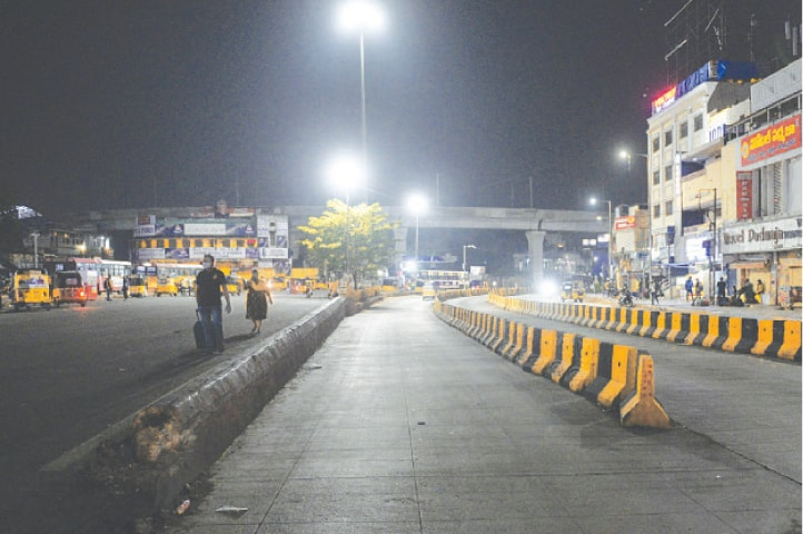 People walk along a deserted road in Hyderabad during a night curfew imposed by the government of Telangana state amidst rising coronavirus cases.—AFP
