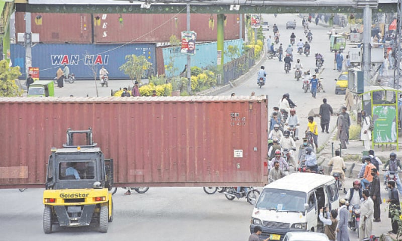 ISLAMABAD: Motorcyclists make their way through an opening on the road as municipal workers begin removing shipping containers placed near the Faizabad interchange after the authorities reached an understanding with the Tehreek-i-Labbaik Pakistan on Tuesday.—Online
