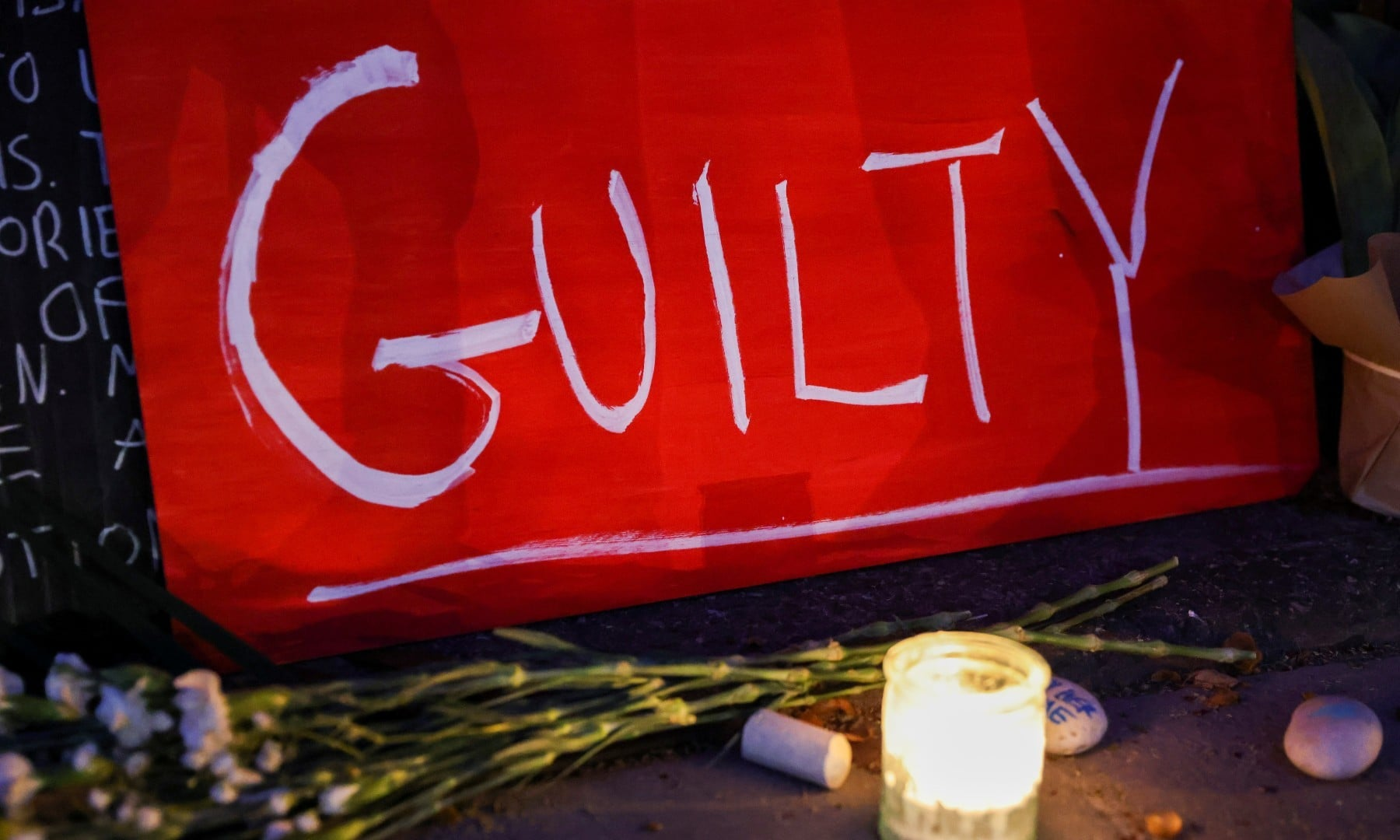 "A sign reading ""GUILTY"" rests next to a candle at Carl Schurz Park after the verdict in the trial of former police officer Derek Chauvin, found guilty of the death of George Floyd on April 20. —  Reuters"