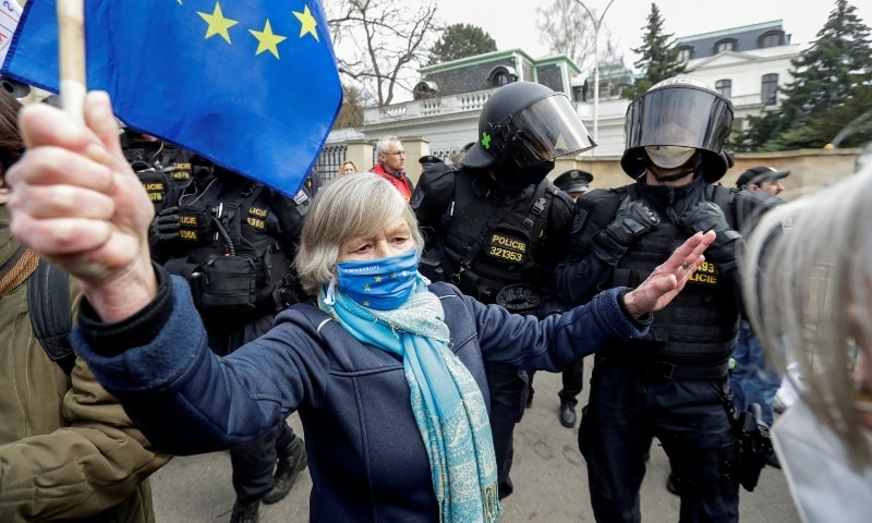A woman holds an EU flag next to police officers during a protest over the Russian intelligence services alleged involvement in an ammunition depot explosion in Vrbetice area in 2014, outside the Russian Embassy in Prague on April 18. — Reuters
