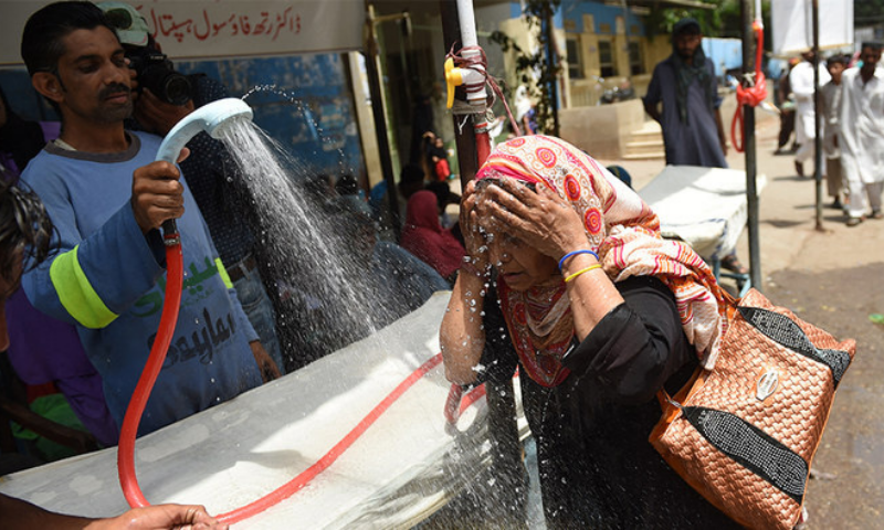 In this file photo, a volunteer showers a woman with water during a heatwave in Karachi. — AFP