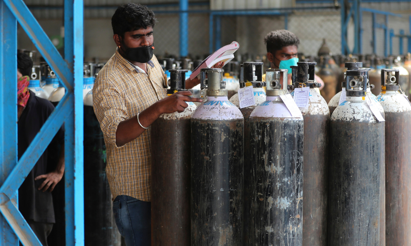 A worker checks oxygen cylinders before they are delivered to different hospitals at a gas supplier facility in Bengaluru, India on Wednesday. — AP