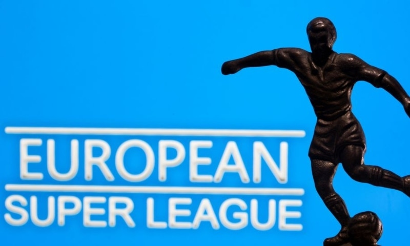 """A metal figure of a football player with a ball is seen in front of the words """"European Super League"""" in this illustration taken April 20. — Reuters"""
