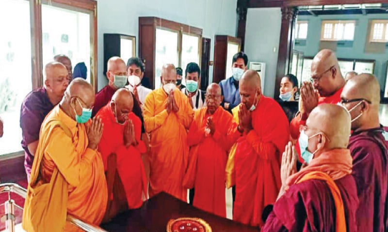Sri Lankan monks perform rituals before relics of Lord Buddha at Taxila museum on Wednesday. — Dawn