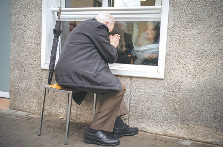 JAVIER Anto prays in front of his wife through a window separating the nursing home from the street in Barcelona.—AP