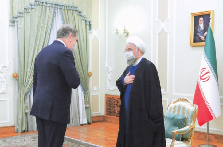 TEHRAN: In this photo released officially, Iranian President Hassan Rouhani welcomes Foreign Minister Shah Mahmood Qureshi before their meeting on Wednesday.—AP