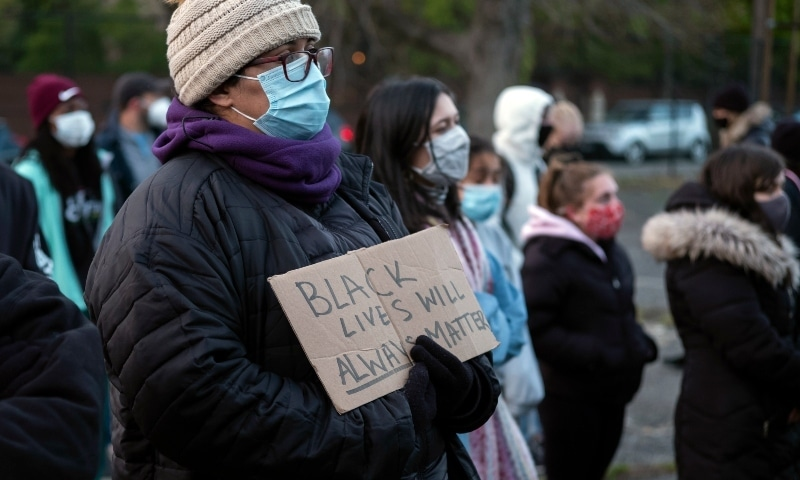 A person holds a sign during a community vigil for 16-year-old Ma'Khia Bryant on April 21 at Douglas Elementary School in Columbus. - AP