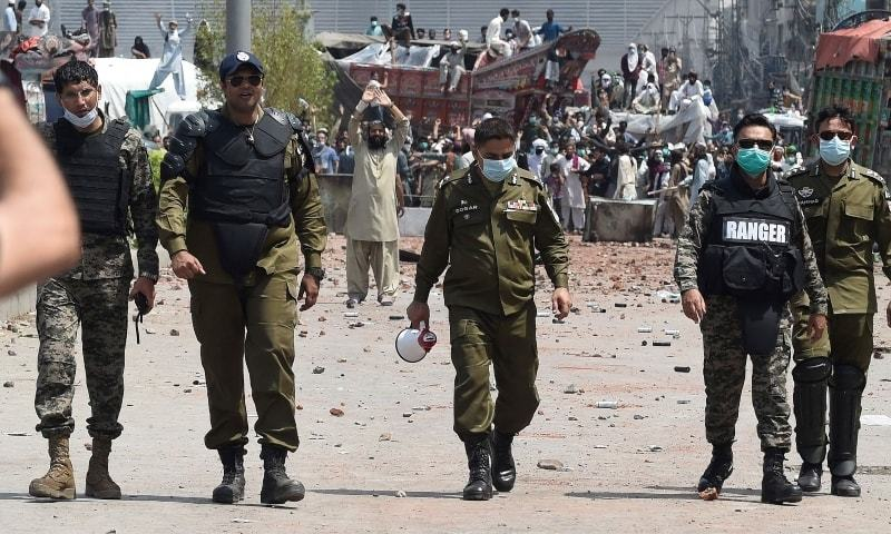Security personnel walk back after having a talk with TLP supporters during a protest along a blocked street in Lahore on Sunday. — AFP/File