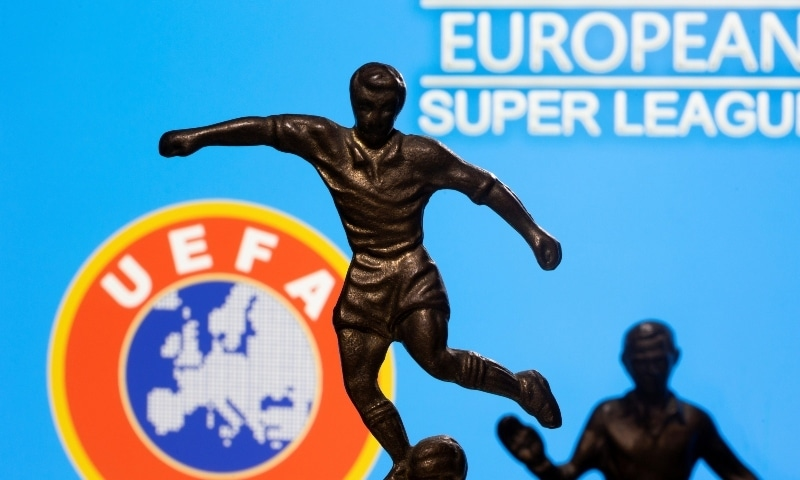 """Metal figures of football players are seen in front of the words """"European Super League"""" and the UEFA logo in this illustration taken April 20. - Reuters"""