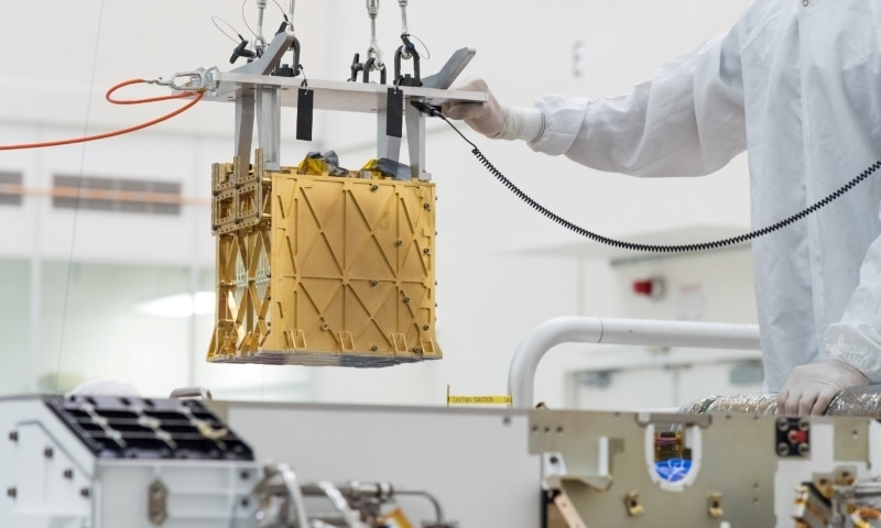 Technicians at Nasa's Jet Propulsion Laboratory lower the Mars Oxygen In-Situ Resource Utilization Experiment (MOXIE) instrument into the belly of the Perseverance rover in an undated photograph in Pasadena. — Reuters