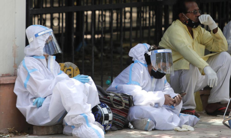People in personal protective suits wait outside a mortuary in India to collect the body of their relative. — AP