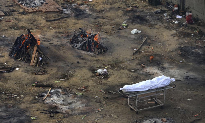 Multiple funeral pyres of those patients who died of Covid-19 disease are seen burning in a ground in India. — AP
