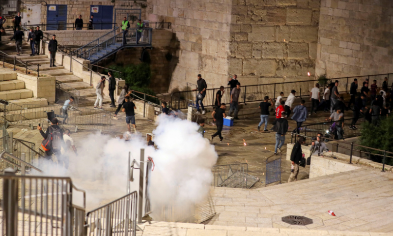 Palestinians run away as a stun grenade fired by Israeli police explodes during clashes at Damascus Gate just outside Jerusalem's Old City during Ramazan. — Reuters