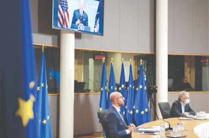 BRUSSELS: US President Joe Biden (on screen) speaks as European Council's President Charles Michel attends the summit on climate change via a video conference app on Thursday.—AFP