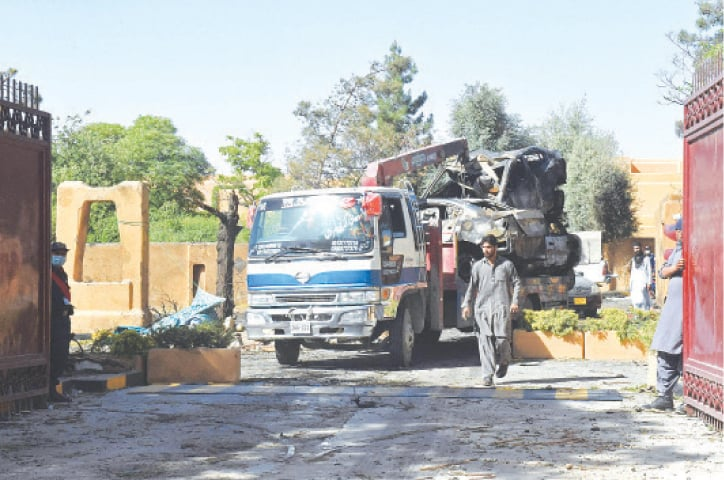 A TRUCK transports damaged vehicles from Serena Hotel, a day after a deadly suicide blast struck the building, on Thursday.—AFP