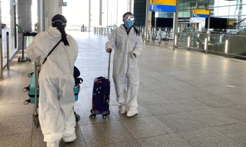 Passengers wearing protective clothing are seen at Heathrow Airport on May 22, 2020. — Reuters