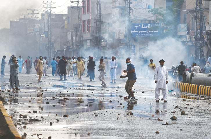 In this file photo, a supporter of Tehreek-i-Labbaik Pakistan prepares to throw a stone towards the police (not seen) during a protest in Lahore.— AFP/File