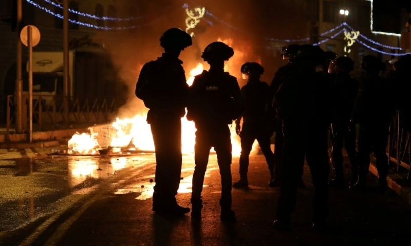 Israeli police officers stand next to a burning barricade during clashes with Palestinians, as the Muslim holy fasting month of Ramazan continues, in Jerusalem, Israel, April 22. — Reuters