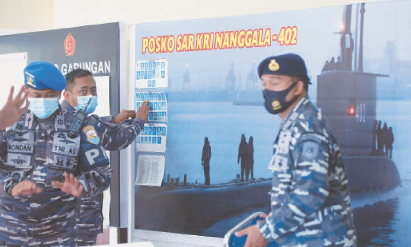 Indonesian military officials set pictures of the missing submarine before a news briefing at an airport on Friday.—AP