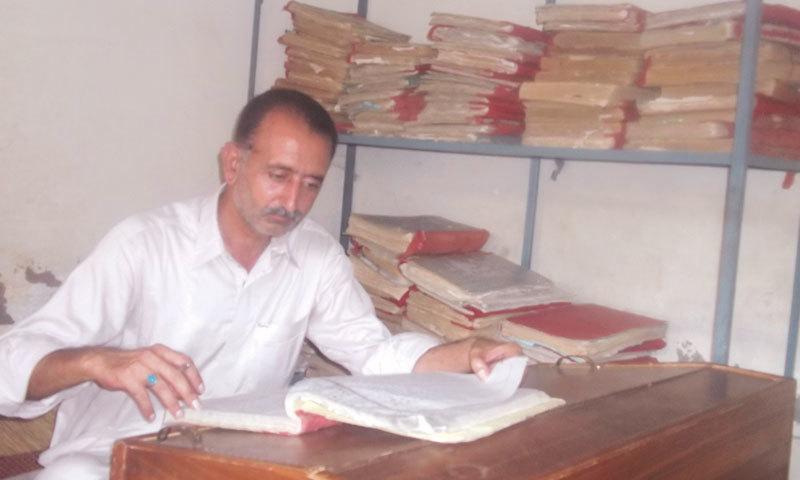A Patwari working at his rented office in Chakwal. — Dawn/File