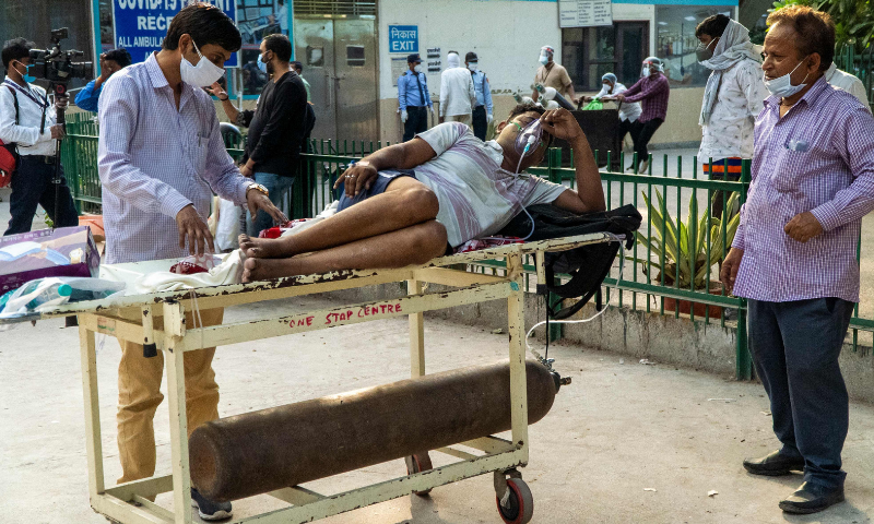 Relatives wait next to a Covid-19 patient laying on a stretcher in a hospital complex for admission in New Delhi, India on Saturday. — AFP