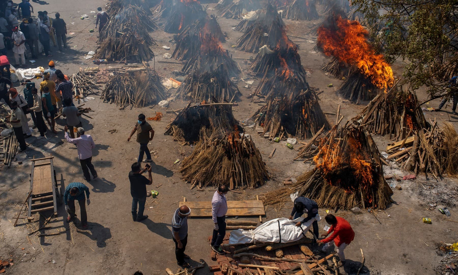 Multiple funeral pyres of victims of Covid-19 burn at a ground that has been converted into a crematorium for mass cremation in New Delhi on April 24. —  AP