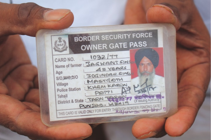 Jagwant Singh holds up his gate pass that allows him to cross the border | Neha Thirani Bagri