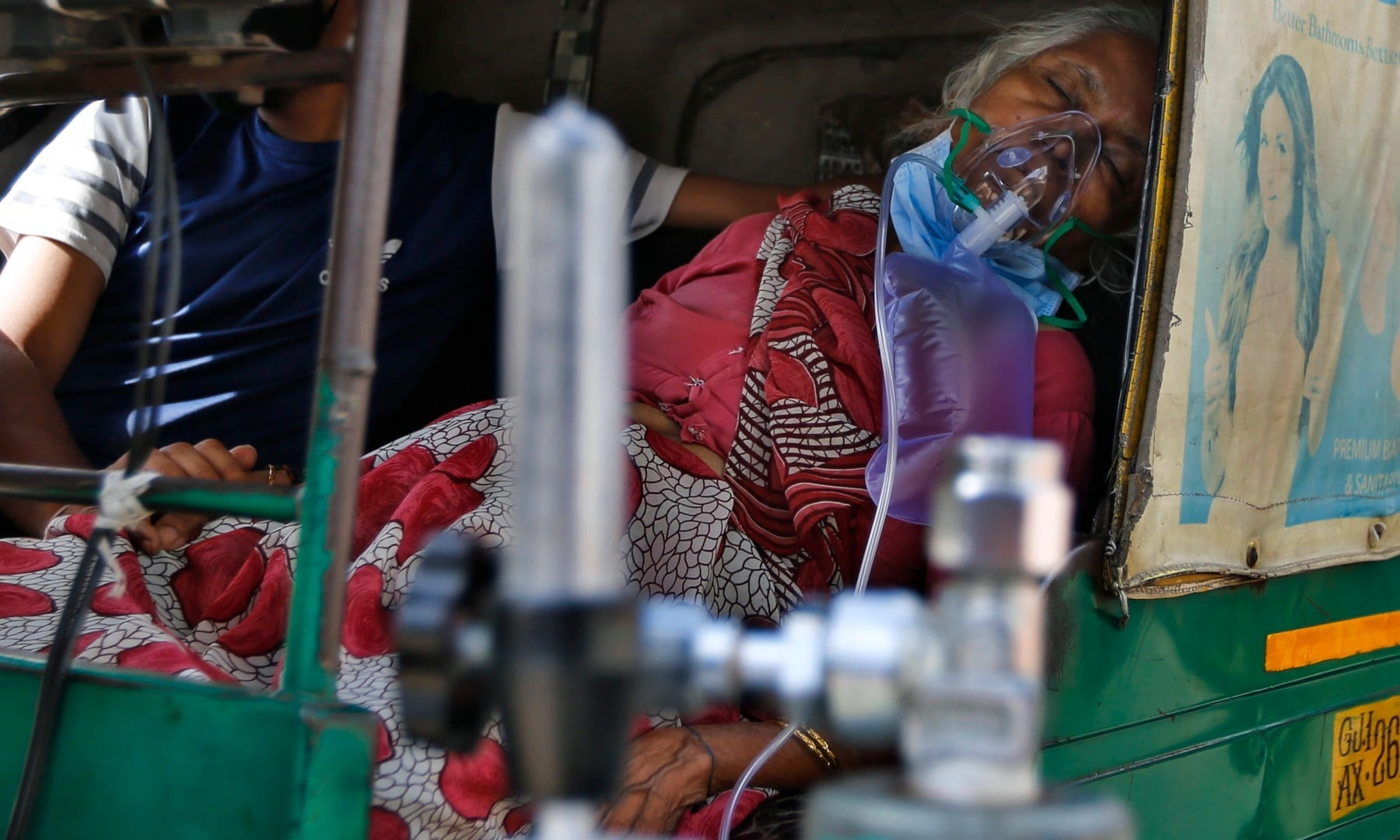 A Covid-19 patient breathes with the help of an oxygen mask and waits inside an auto rickshaw to be attended to and admitted to a dedicated coronavirus government hospital in Ahmedabad on April 17. — AP