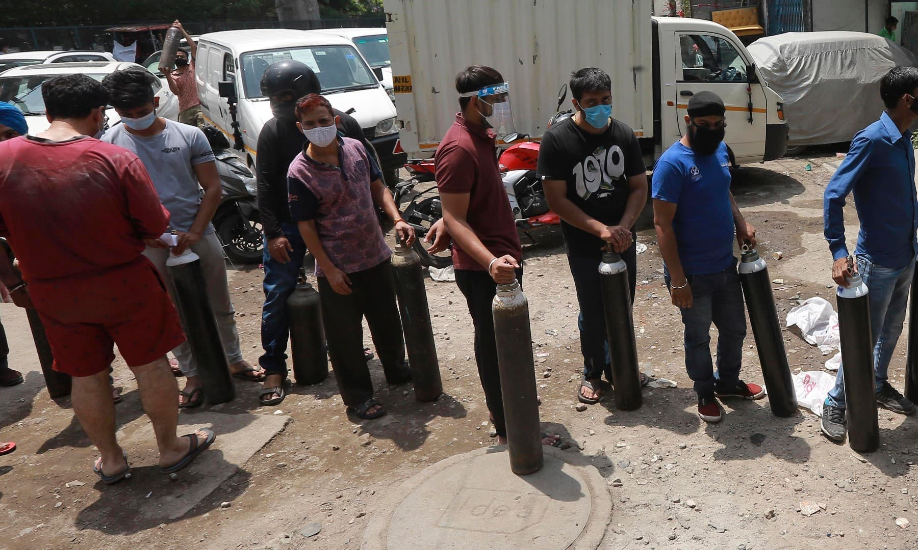 People stand in queues to refill oxygen in cylinders in New Delhi on April 23. — AP