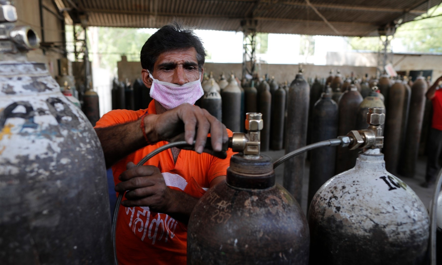 A worker refills medical oxygen cylinders at a charging station on the outskirts of Prayagraj on April 23. — AP