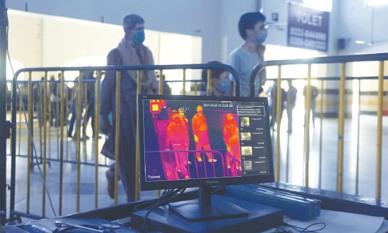 Passengers walk through a thermal scanner installed at a railway station in Lahore to check coronavirus symptoms as 86,529 active cases were recorded across the country on Saturday. — AP