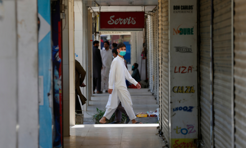 A man wearing a face mask walks through a market closed due to new government restrictions to control the spread of the coronavirus, in Islamabad on Saturday. — AP