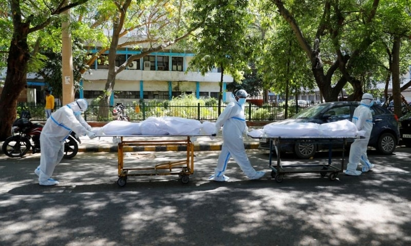 Health workers wearing personal protective equipment carry bodies of people who were suffering from Covid-19, outside the Guru Teg Bahadur hospital, in New Delhi, India on Saturday. — Reuters