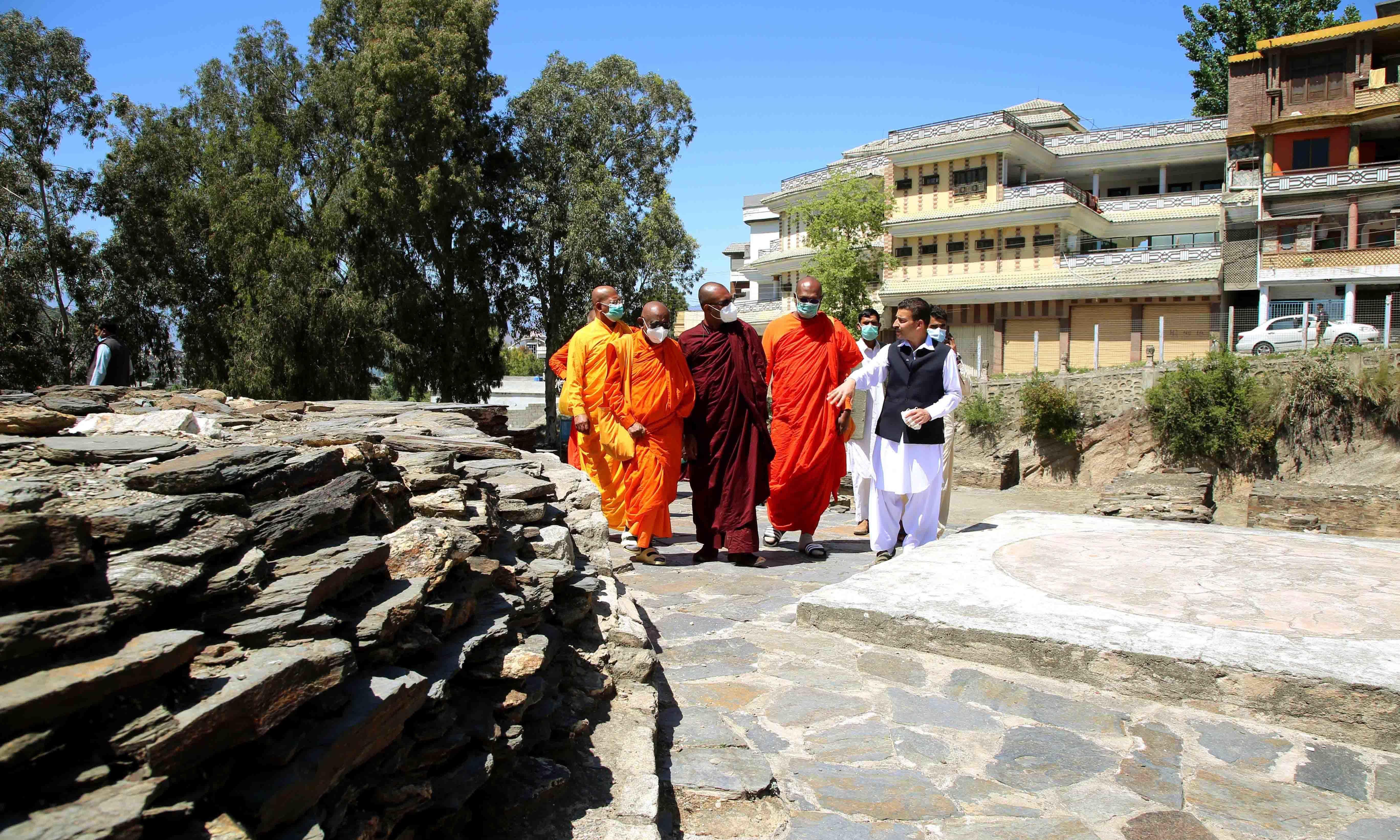 مقاماتِ آثارِ قدیمہ کے انچارج سوات، راہبوں کو خانقاہ کے بارے میں تفصیلات بتا رہے ہیں—تصویر امجد علی سحاب