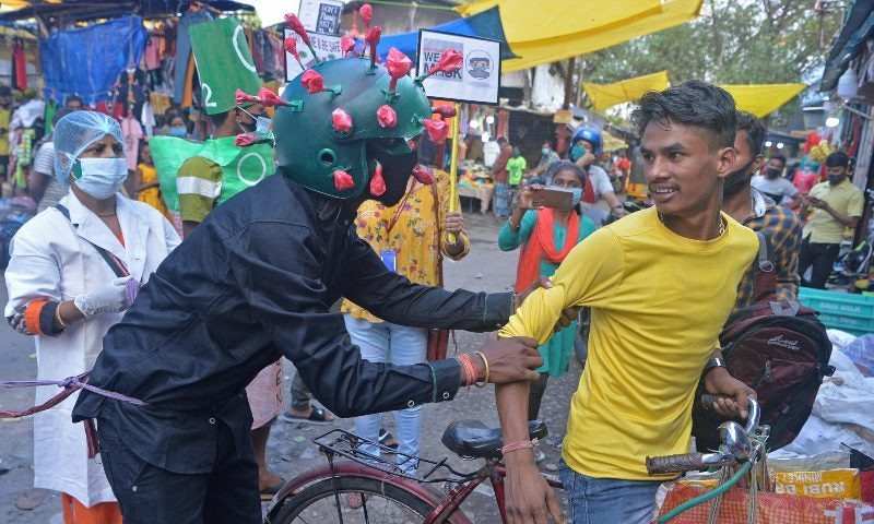 A man from a non-governmental organisation (NGO) wearing an outfit resembling the coronavirus moves around a marketplace urging people to follow the safety protocols during an awareness drive held in Siliguri, India on April 25. — AFP