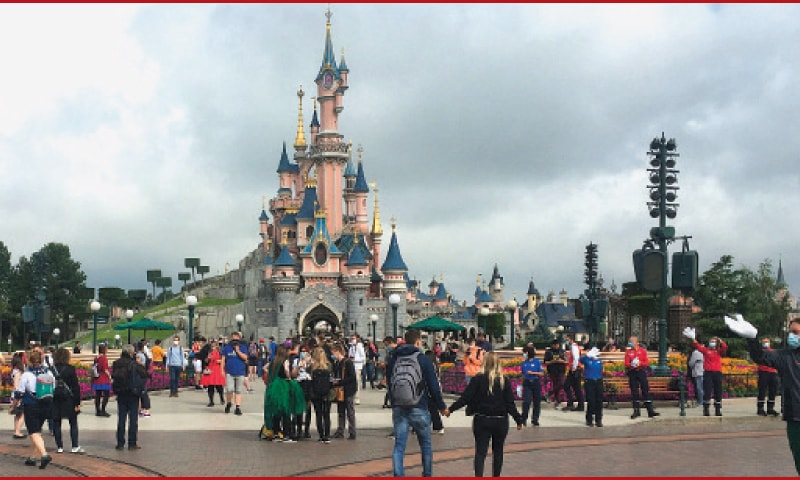Visitors and staff wearing protective face masks walk down the Main Street of Disneyland Paris in Marne-la-Vallee on the outskirts of Paris last year. Disneyland Paris, normally Europe's biggest tourist attraction hosts a mass Covid vaccination site at its convention centre as France seeks to speed up its inoculation drive, officials said last week. The amusement park east of the capital has been closed since October 30, when non-essential businesses were ordered to close amid a surge in infections, putting its 17,000 employees out of work.—AFP