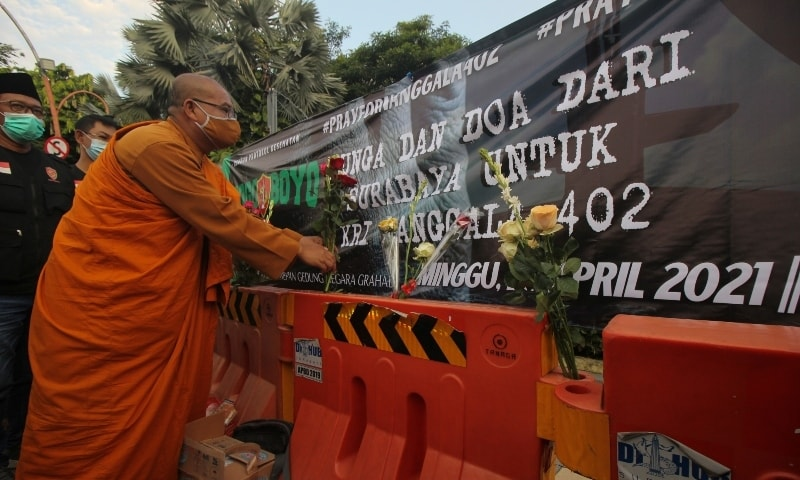 A monk puts flowers during a prayer for the missing Indonesian Navy KRI Nanggala-402 submarine in Surabaya on April 25. — Reuters