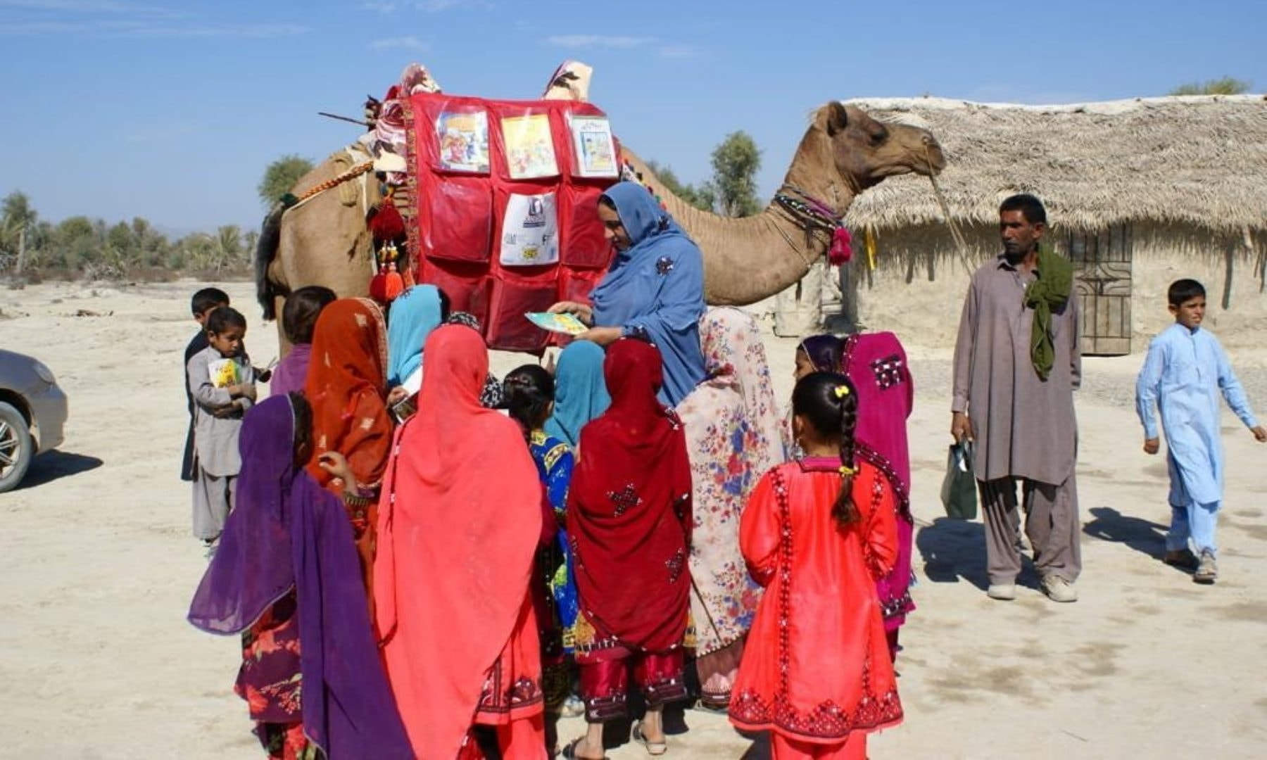 Children stand next to a camel that brought books in Mand, Balochistan, April 11. — Fuzul Bashir via Reuters