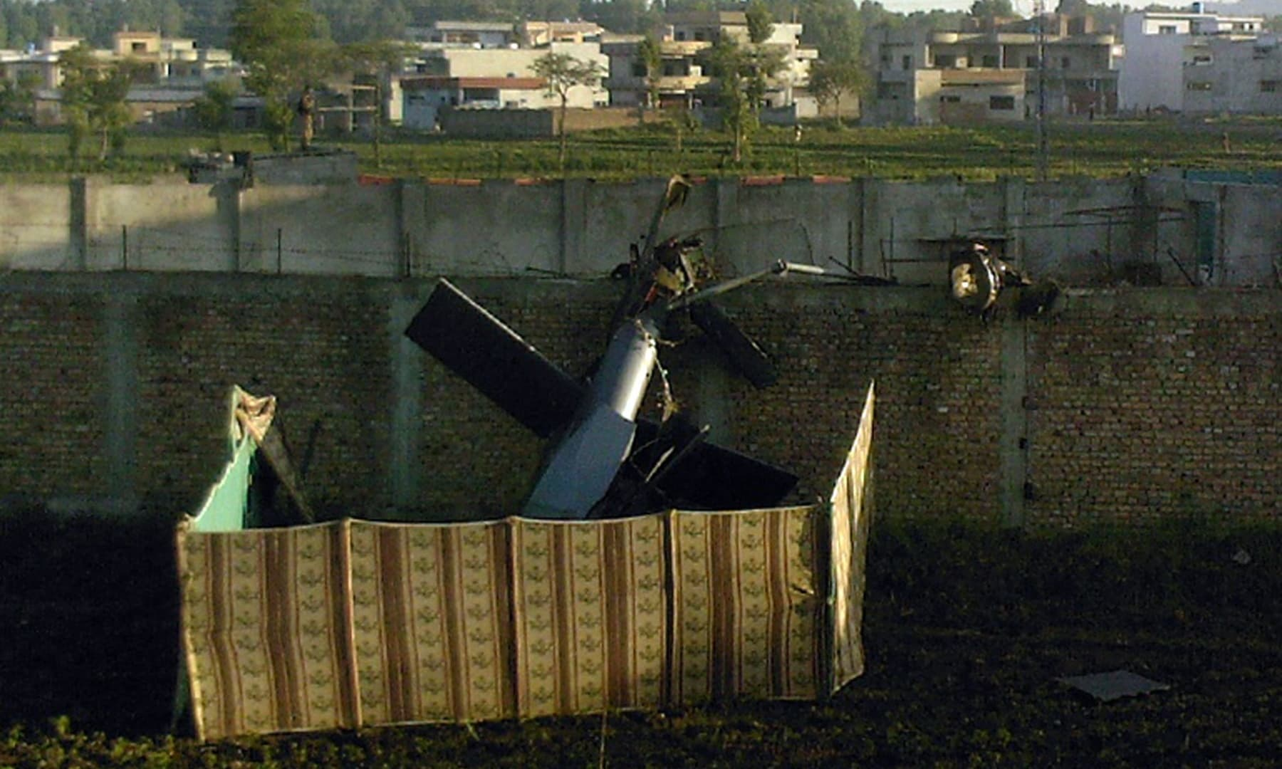 In this file photograph taken on May 2, 2011, a crashed military helicopter is seen near the hideout of Al Qaeda leader Osama bin Laden after a ground operation by US Special Forces in Abbottabad. — AFP