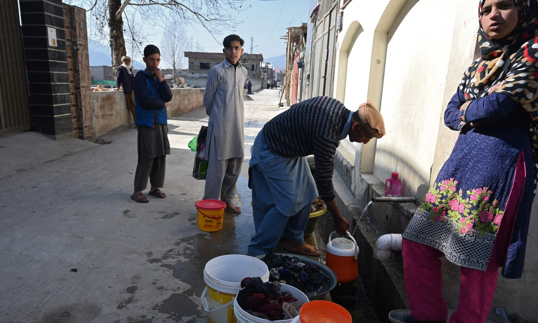 In this picture taken on February 11, 2021, local residents and neighbours of slain former Al Qaeda leader Osama bin Laden, wait for their turn to collect water from a pipe near the site of the demolished compound of Bin Laden, in northern Abbottabad. — AFP